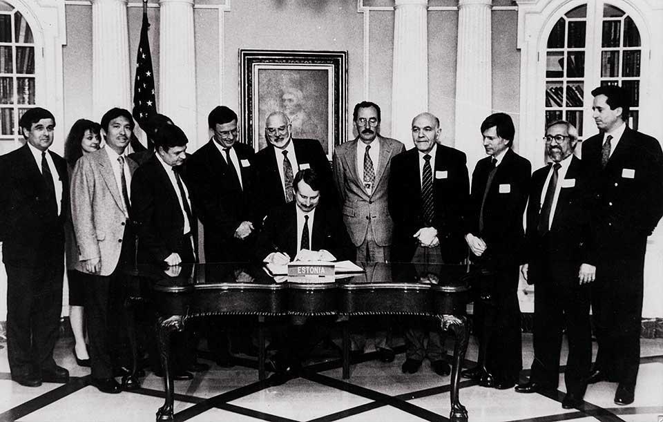 Eesti Panga president Siim Kallas (keskel) dokumendile alla kirjutamas. Allikas: Vambola Salupuu